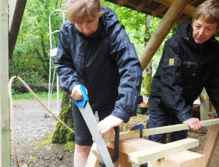 sawing wood on a tiny house course