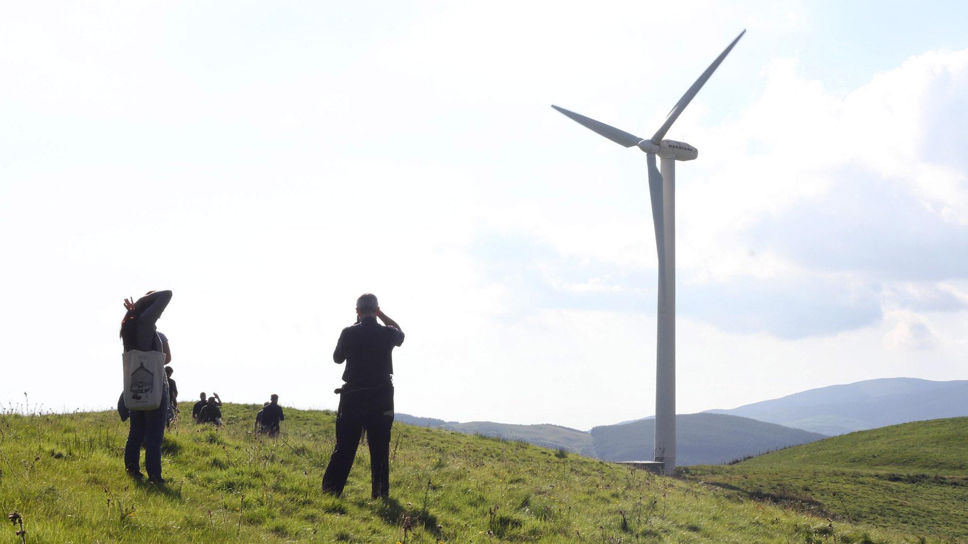 CAT students walking towards a wind turbine